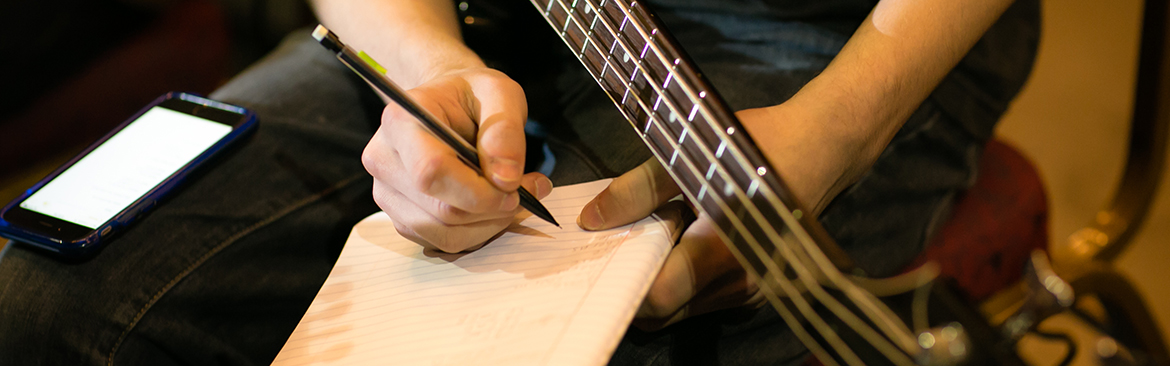 A Songwriters Lab participant writes lyrics while holding a guitar.