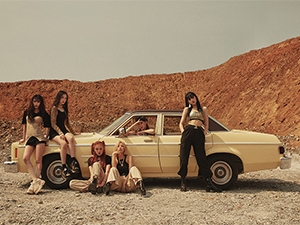 The band pose around an old car in a desert.