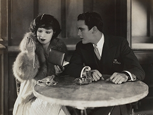 Still image from Get Your Man, with a couple sitting at a table.