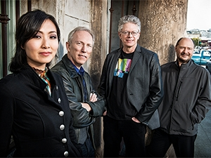 Kronos Quartet standing and looking at camera.