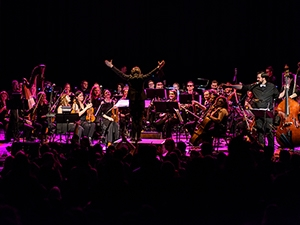 Seattle Rock Orchestra performing on stage, led by a conductor.