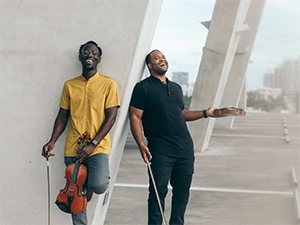 Musicians leaning against a concrete structure, holding violins and laughing.