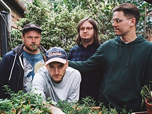 Four band members standing near plants.
