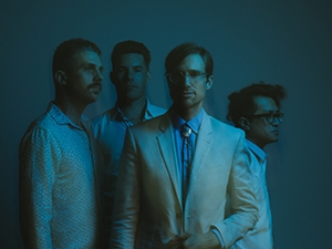 Four band members standing, bathed in blue light.