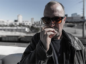 Doug Stanhope wearing sunglasses and smoking a cigarette.