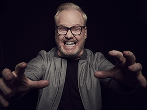 Jim Gaffigan grimacing with his hands out in front of him.