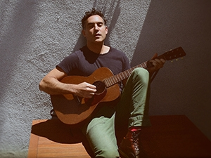 Joshua Radin playing the guitar while leaning against a wall.