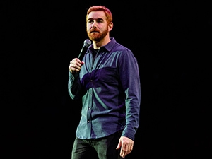 Andrew Santino on stage with a microphone.