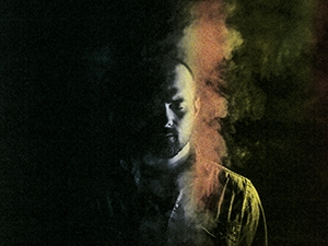 Ásgeir with his eyes closed, shown in half light.
