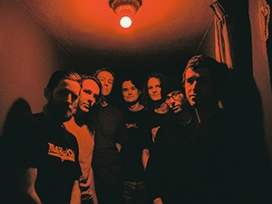 The band standing in a hallway lit by one red lightbulb.
