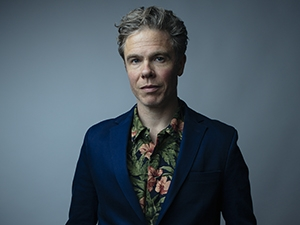 Josh Ritter looking at camera, wearing a blazer.