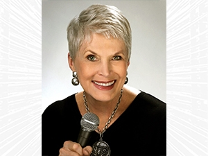Jeanne Robertson smiling and holding a microphone.