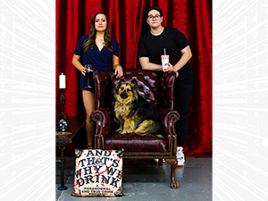 Two people stand behind a chair with a dog and a pillow
