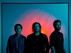 Three band members in a frame of blue light with a sunburst behind them.