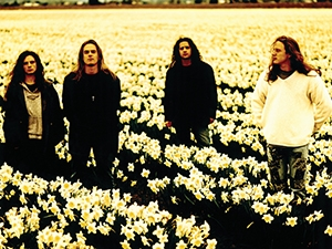 Four band members standing in a field of tulips.