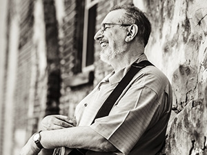 David Bromberg leaning against a wall and laughing.