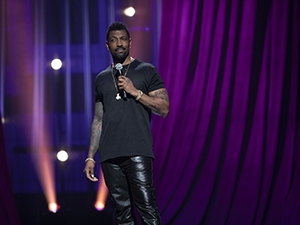 Deon Cole standing on stage with a microphone.