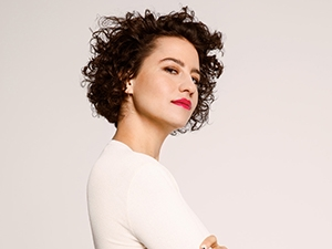 Ilana Glazer staring at camera with arms crossed.