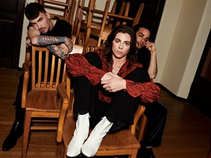 Three band members sitting on wooden chairs.