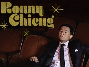 Ronny Chieng wearing a suit and reclining in red theater seats.