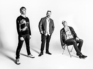 Black and white photo of Stephen Malkmus standing with two other band members.