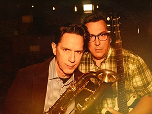 John Flansburgh and John Linnell holding instruments and looking at the camera.