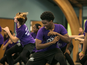 Dancers in purple shirts in motion
