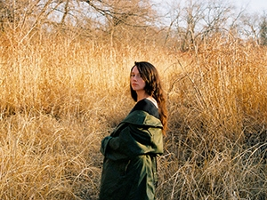 Katie Crutchfield in a long olive green coat, standing in a golden field.