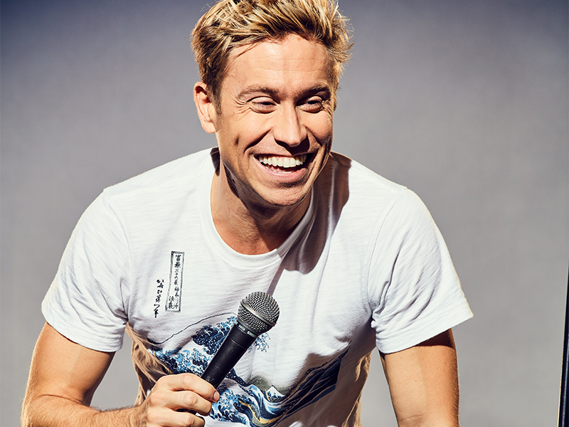 Russell Howard holding a microphone, crouched down and laughing.