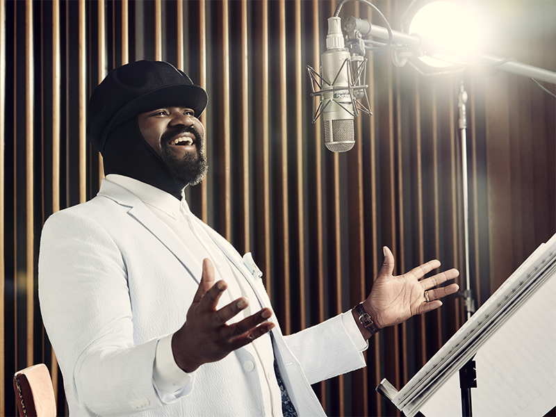 Gregory Porter singing into a microphone with palms turned up