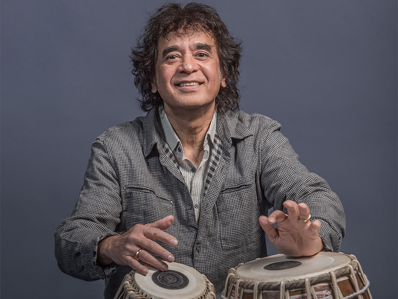 Zakir Hussain playing the tabla and smiling at the camera.