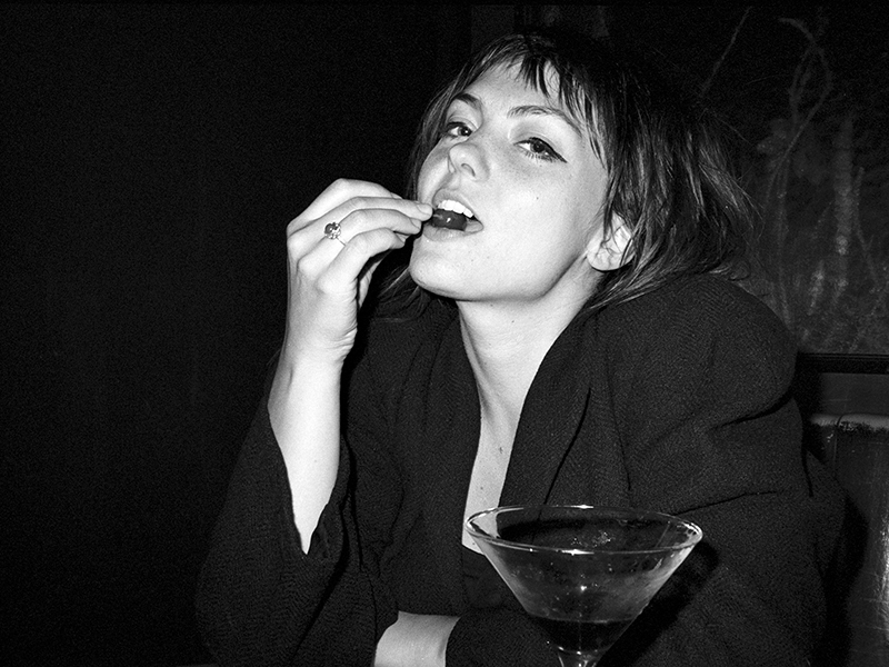 Angel Olsen sitting with a martini and eating a cherry