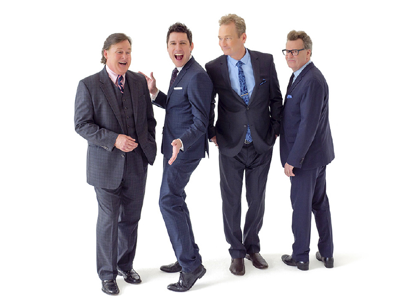 Four hosts wearing suits and smiling.