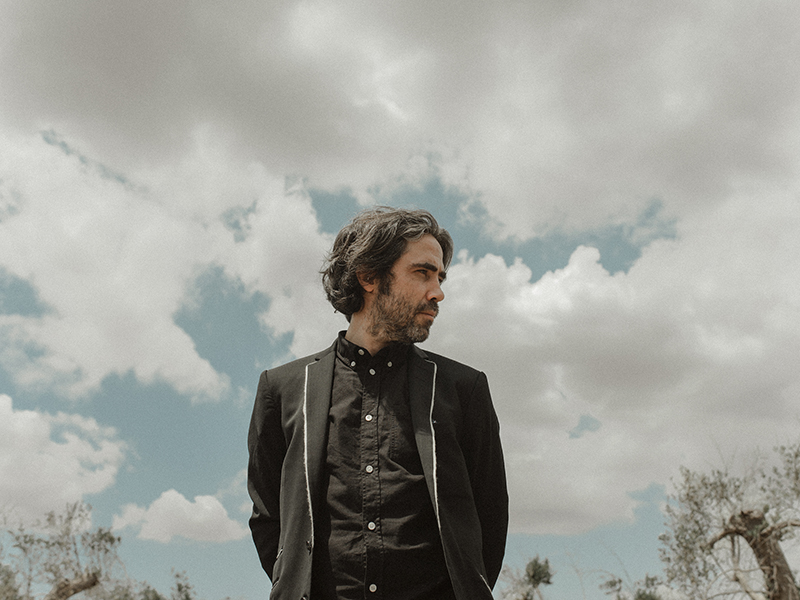 Patrick Watson standing in front of a cloudy sky