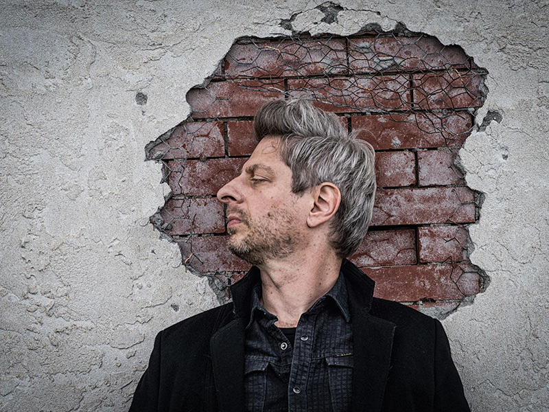 Mike Gordon in side profile in front of a brick wall