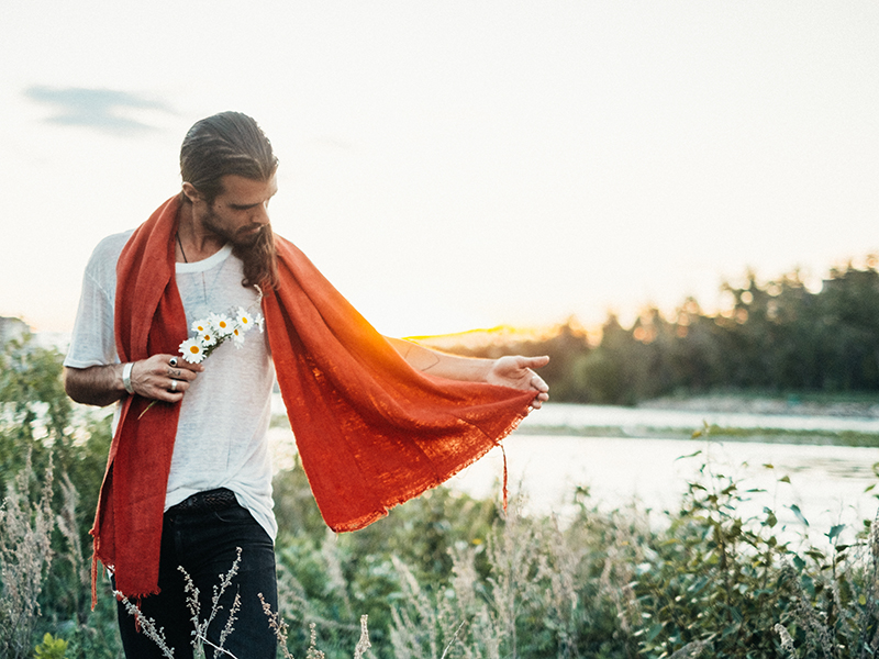 Reuben Bullock standing next to a body of water, wearing an orange scarf and holding daisies.
