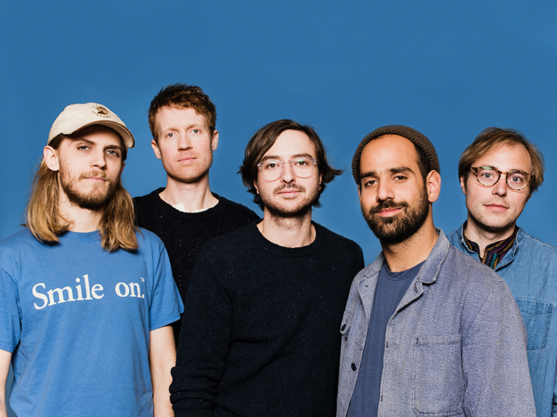 Five band members standing in front of a blue background.