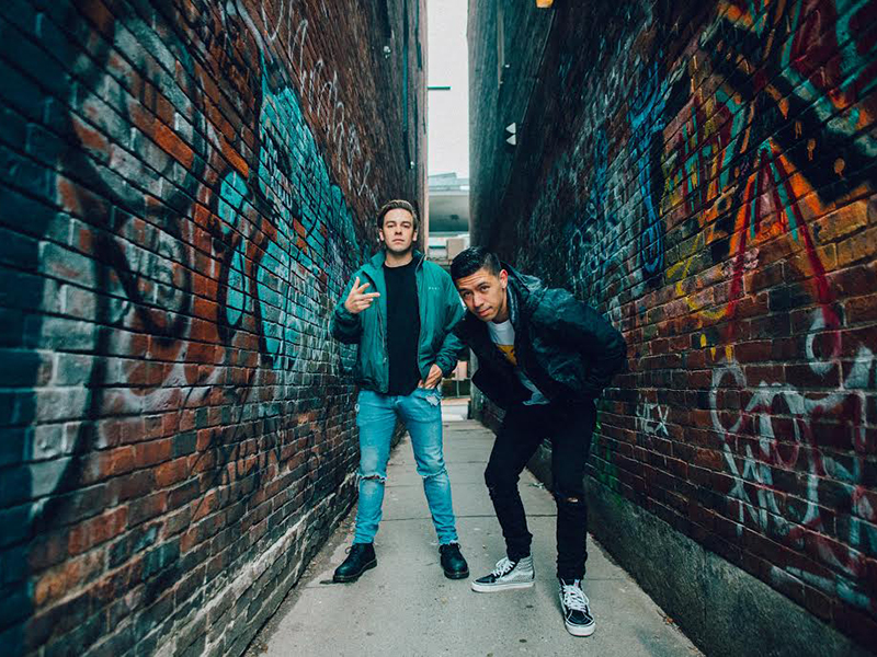 Cody + Noel standing in a narrow alley with graffiti on the walls