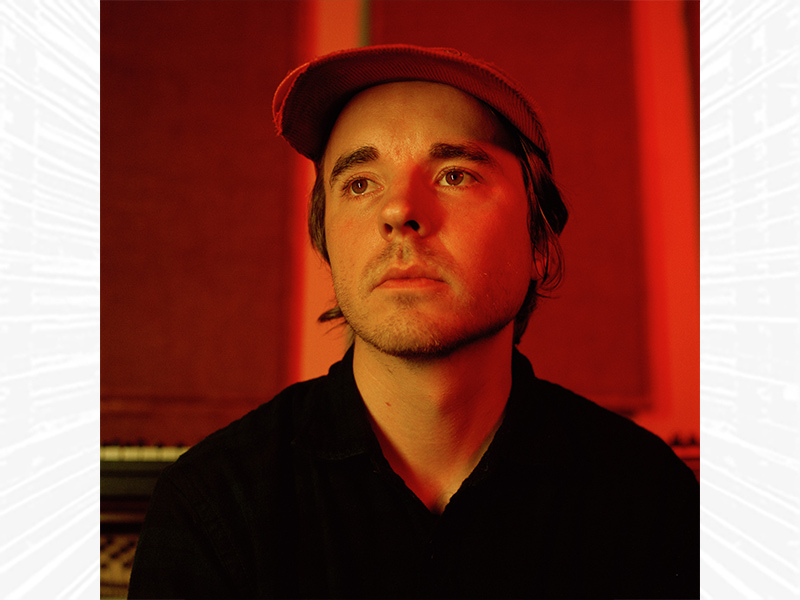 Andy Shauf wearing a ball cap and looking off into the distance.