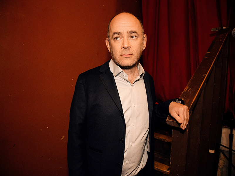 Todd Barry leaning against a staircase.