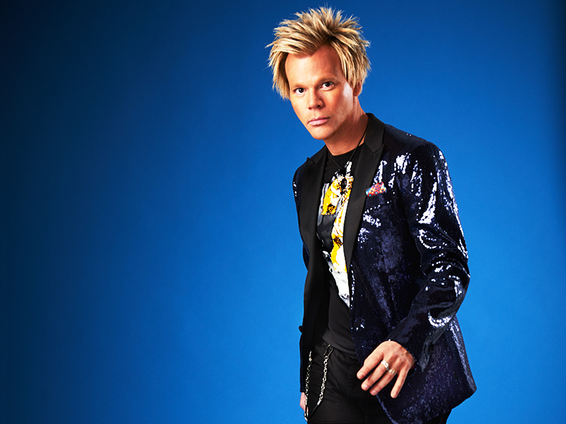 Brian Culbertson standing in front of a blue background.