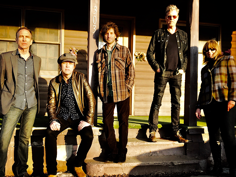 Five band members standing on a porch in the sun.