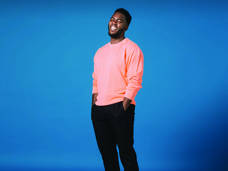Mo Gilligan standing with his hands in his pockets, laughing in front of a blue background.