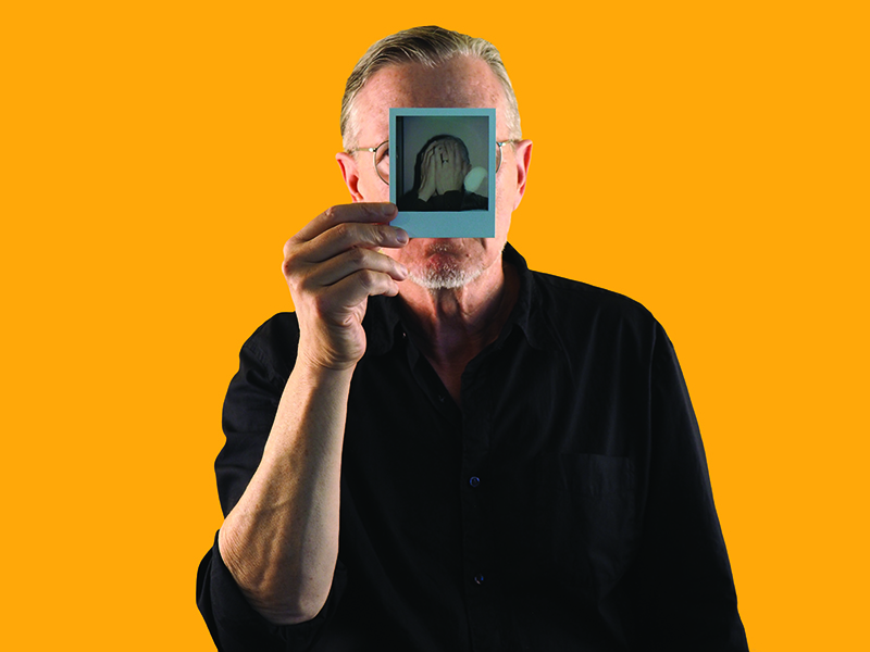 Michael Gira holding a photo of himself covering his face in front of his face.