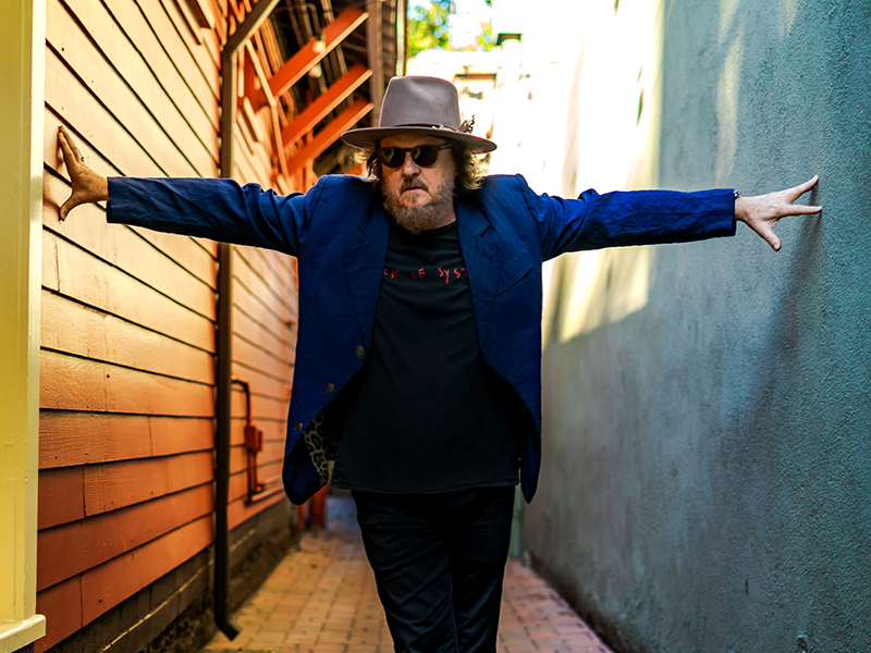 Zucchero standing and stretching his arms to touch the walls on either side of him.