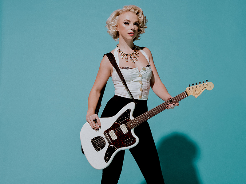 Samantha Fish standing in front of a blue background and holding a guitar.