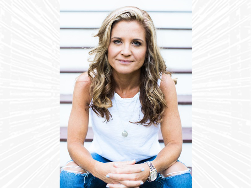 Glennon Doyle seated with arms on knees.