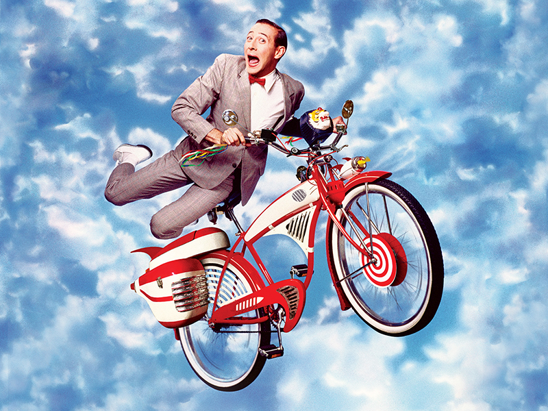 Pee-wee in a suit on a red bike with a blue cloudy sky in the background