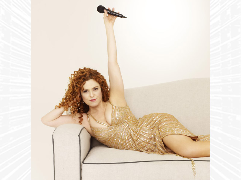 Bernadette Peters on a couch in a sequin dress, holding a microphone in the air.