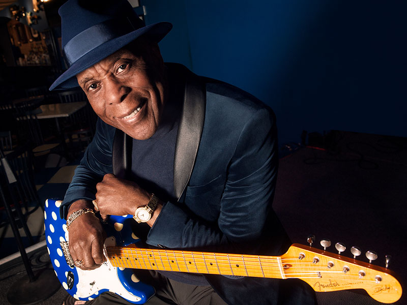 Buddy Guy wearing a fedora and holding a Fender guitar.